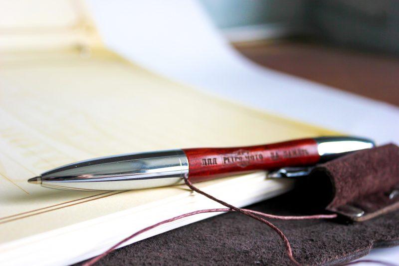 Устроили место хранения ручки на внутренней стороне обложки из кусочка кожи, закрепив декоративными болтами.
