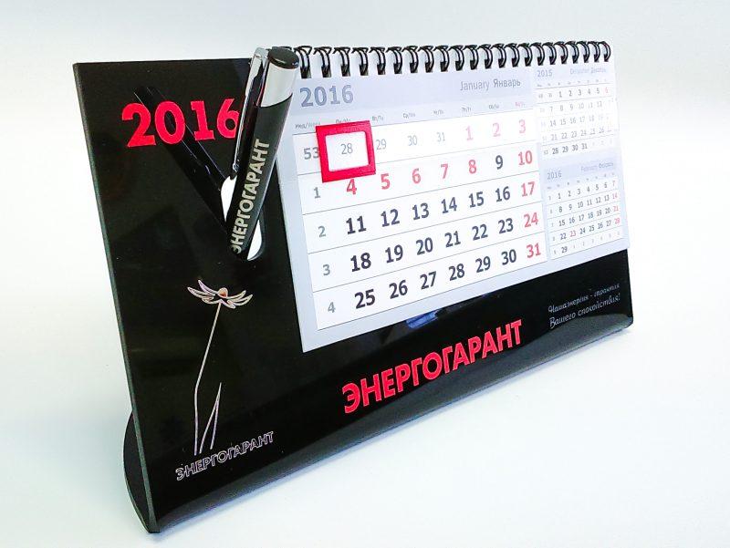 Основа календаря - цветной акрил, что придаёт календарю хорошую устойчивость и солидный вид. На основе информация нанесена лазерной гравировкой и аппликацией ПВХ плёнкой, а логотип выполнен в металле. Основу такого календаря можно использовать многие годы, меняя лишь календарный блок.