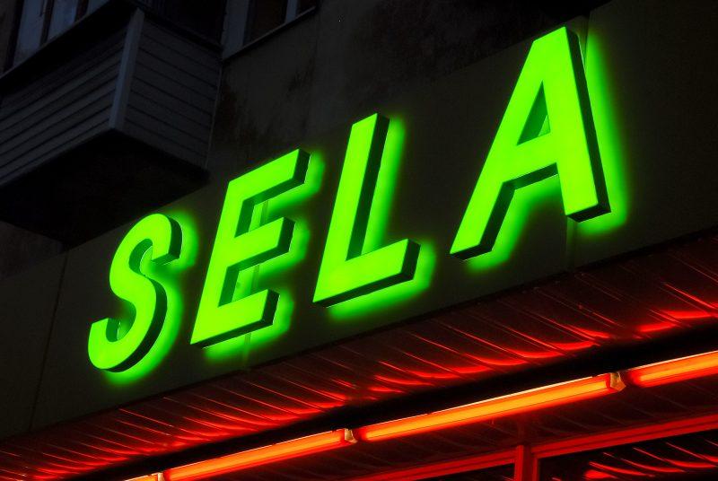 Объемные световые буквы с контражуром «SELA» склеены из акрила и пвх-пластика, оклеены долговечной транслюцентной пвх-пленкой oracal 8500, внутренняя подсветка светодиоды. За счет использования на тыльной стороне акрила с пленкой и удаления буквы от плоскости крепления получаем красивый световой ореол позади буквы, так называемый «контражур». А за счет большого количества диодов подсветка яркая и равномерная. Цель достигнута: салатовая буква хорошо заметна на фризе желтого цвета.